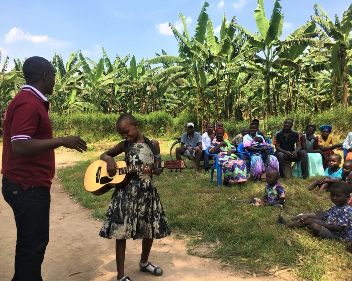 Volunteer teaches young Ugandan child how to play guitar